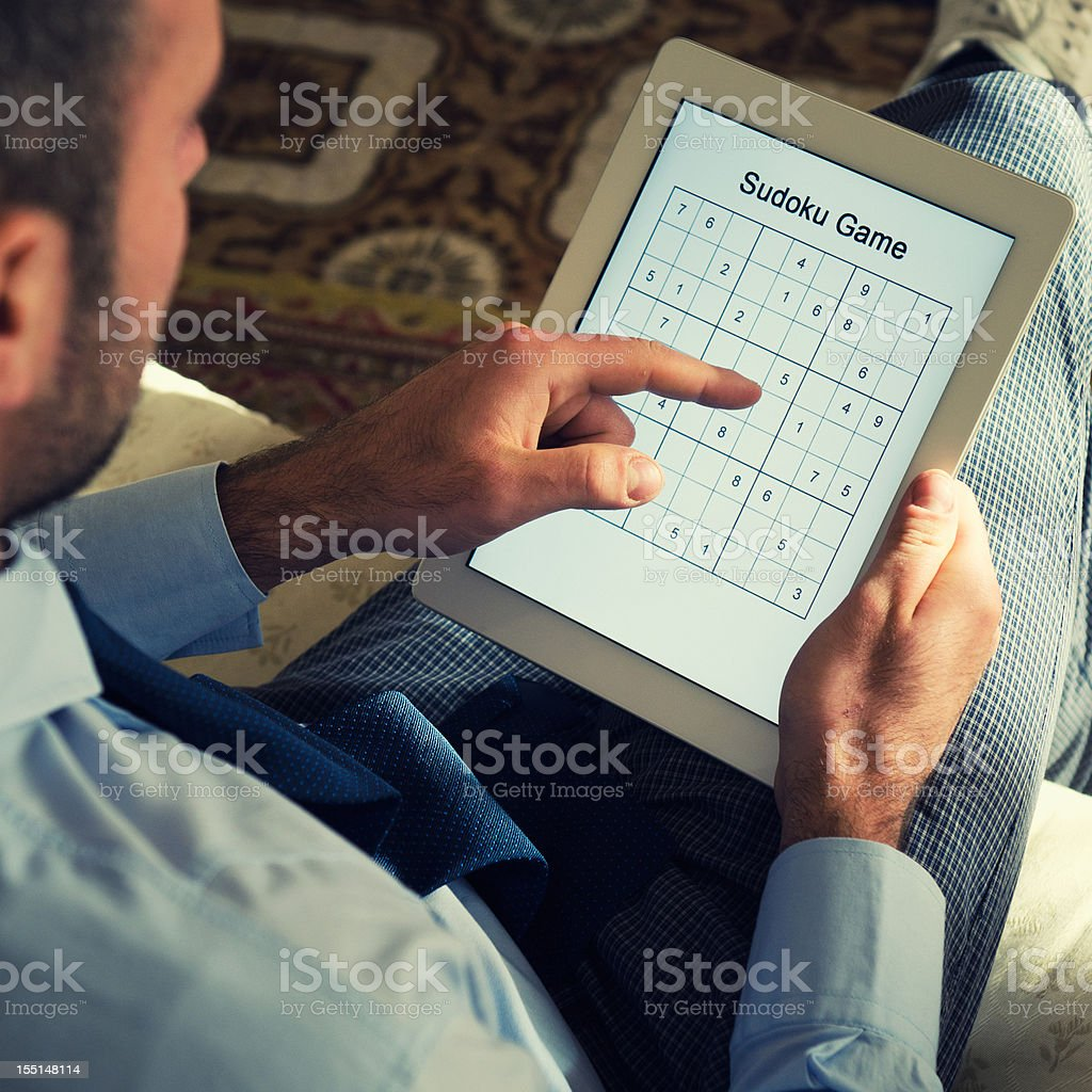 Playing on Sudoku games with digital tablet royalty-free stock photo