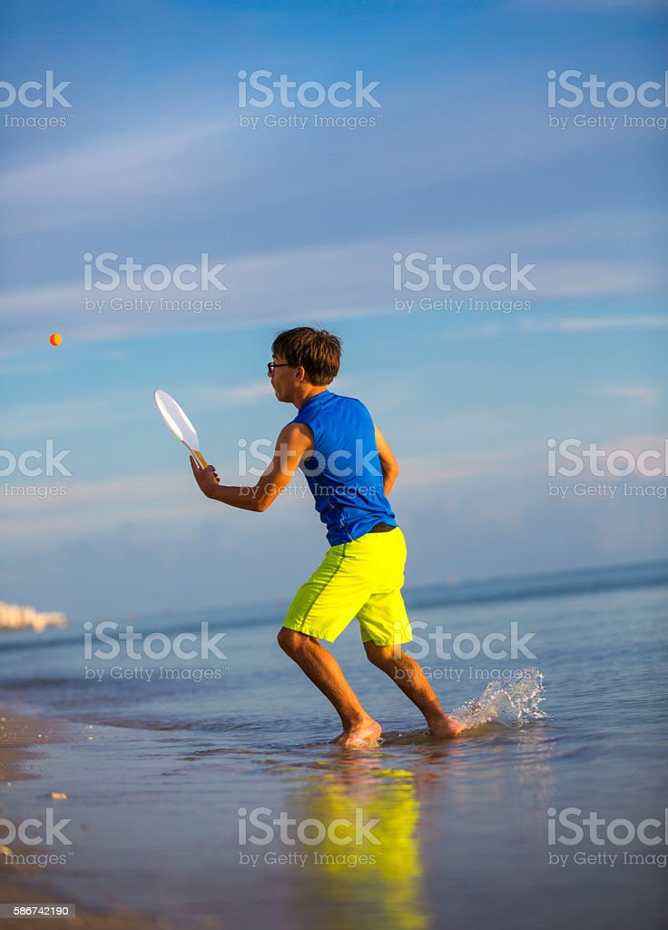 Playing paddle ball at the beach stock photo