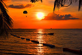 Playing parachute and boat beside the sea on sunset
