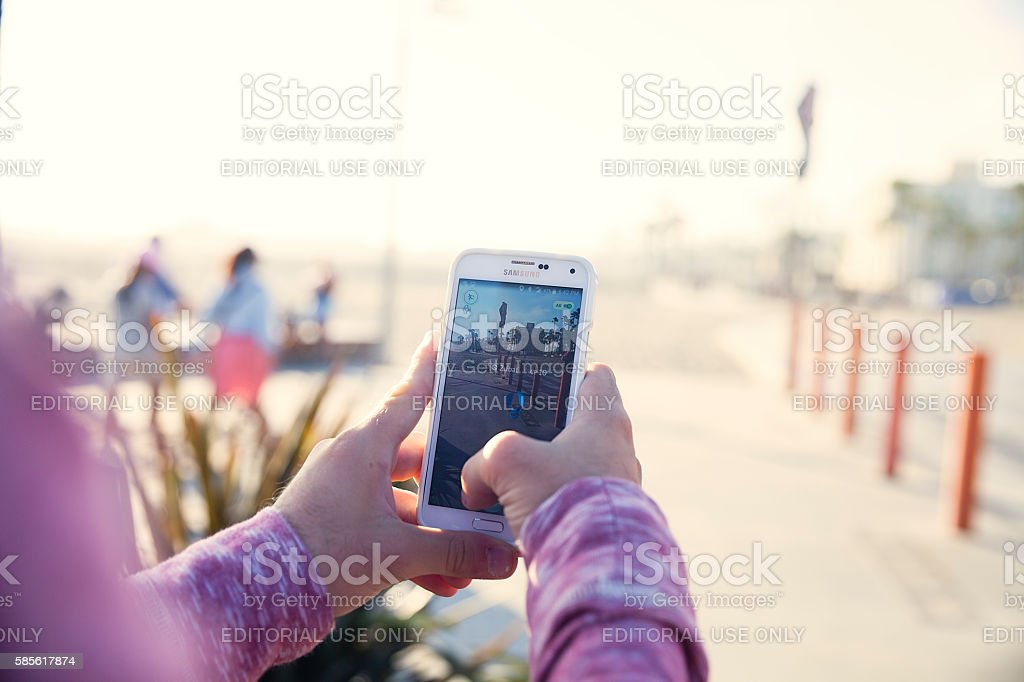 Playing Pokemon Go at the Beach stock photo