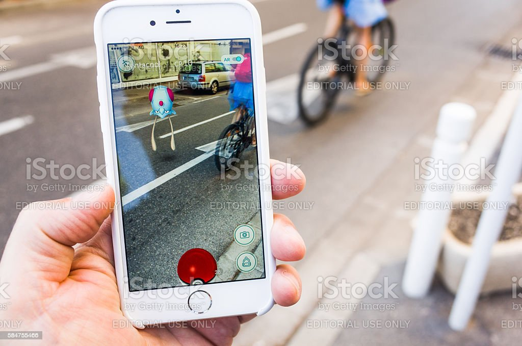 Playing Pokemon Go in the Street stock photo