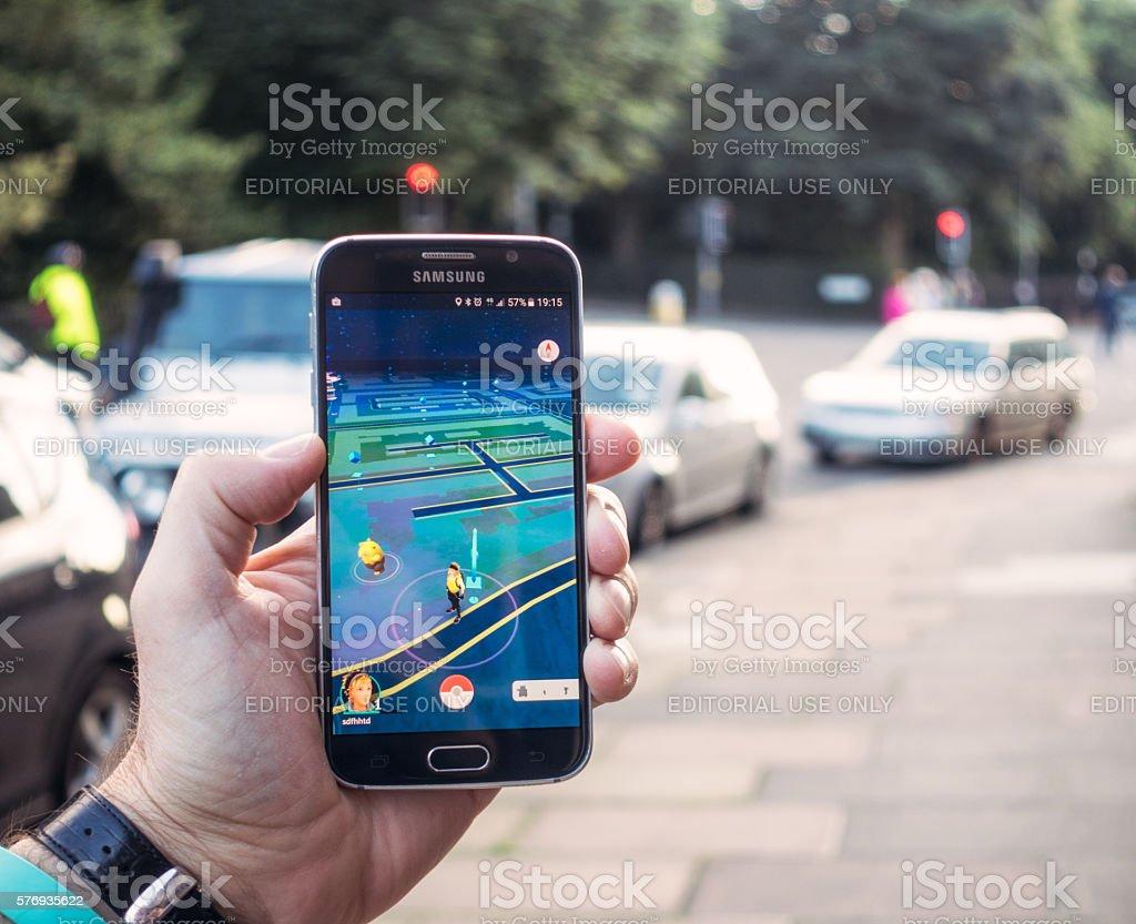 Playing Pokemon Go on the street stock photo