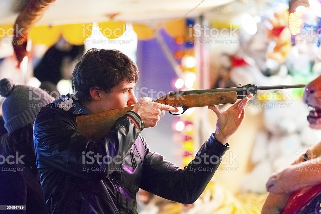 Playing shooting gallery at amusement park royalty-free stock photo