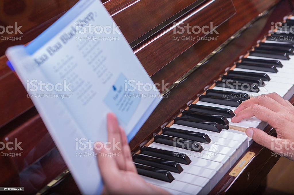 Playing song on piano from a book 2 stock photo