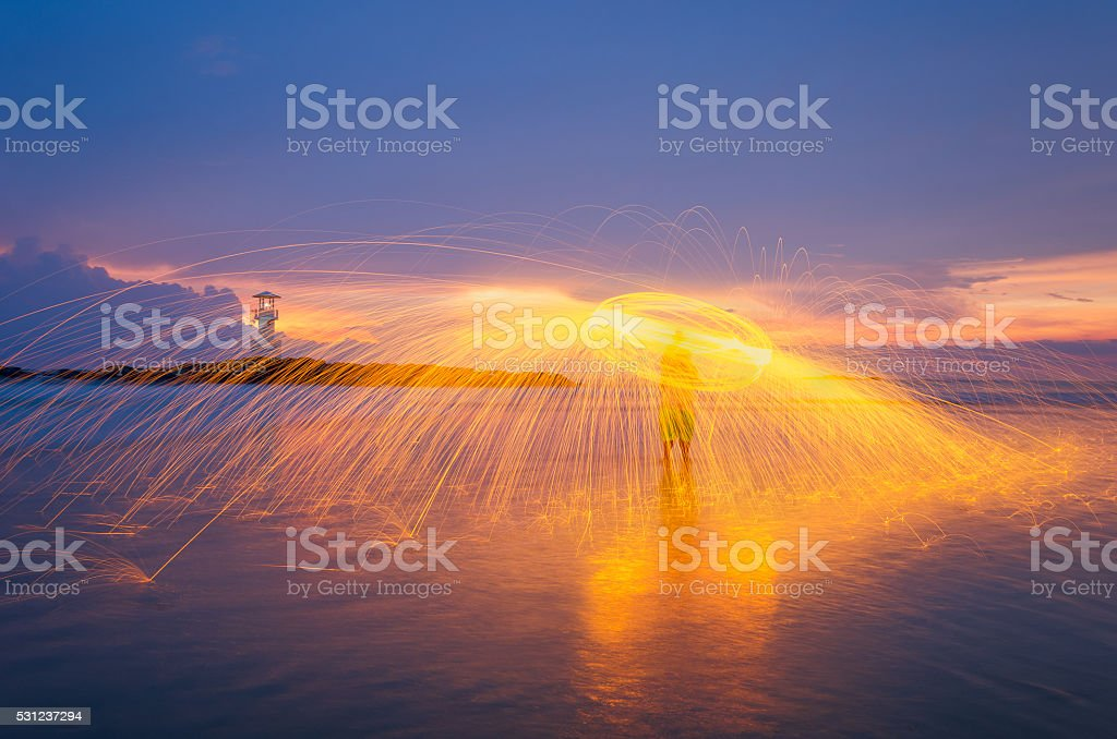 Playing steel wool nearby the lighthouse. stock photo