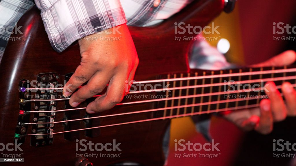 Playing strings of bass guitar stock photo