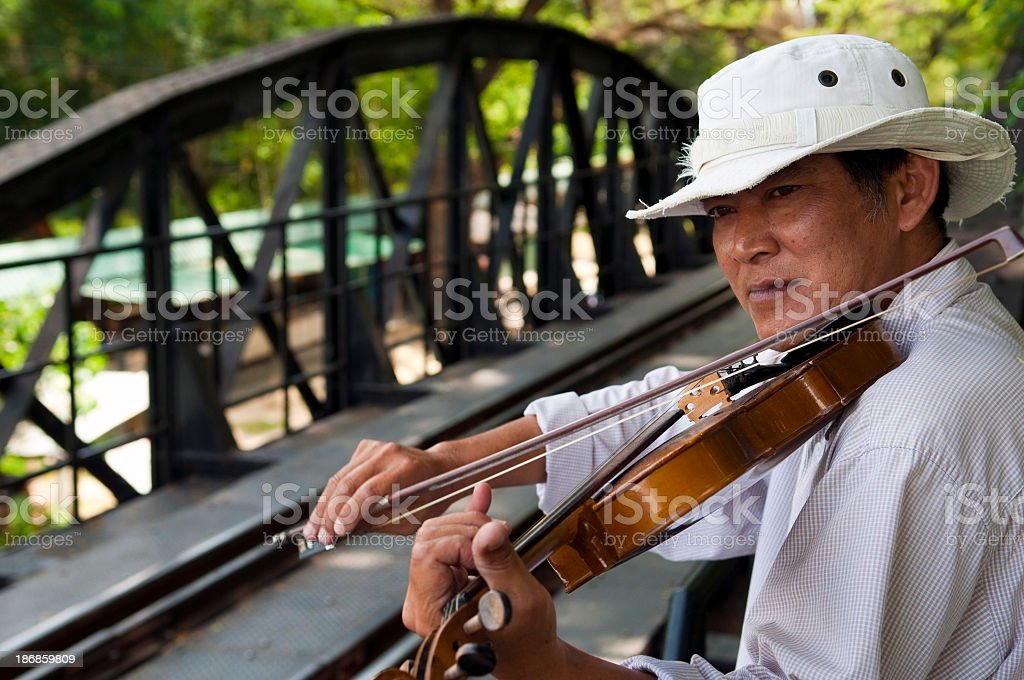 Playing the violin on the Bridge on the River Kwai stock photo