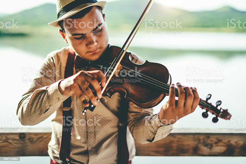 Playing violin by the lake stock photo
