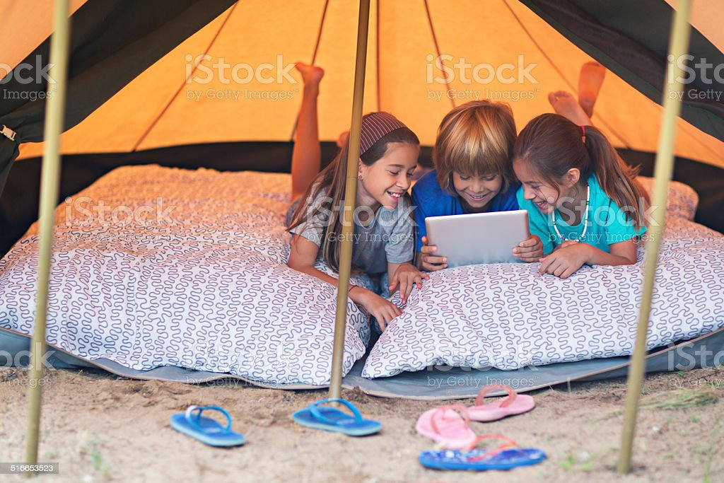 Playing with the digital tablet in the camping stock photo