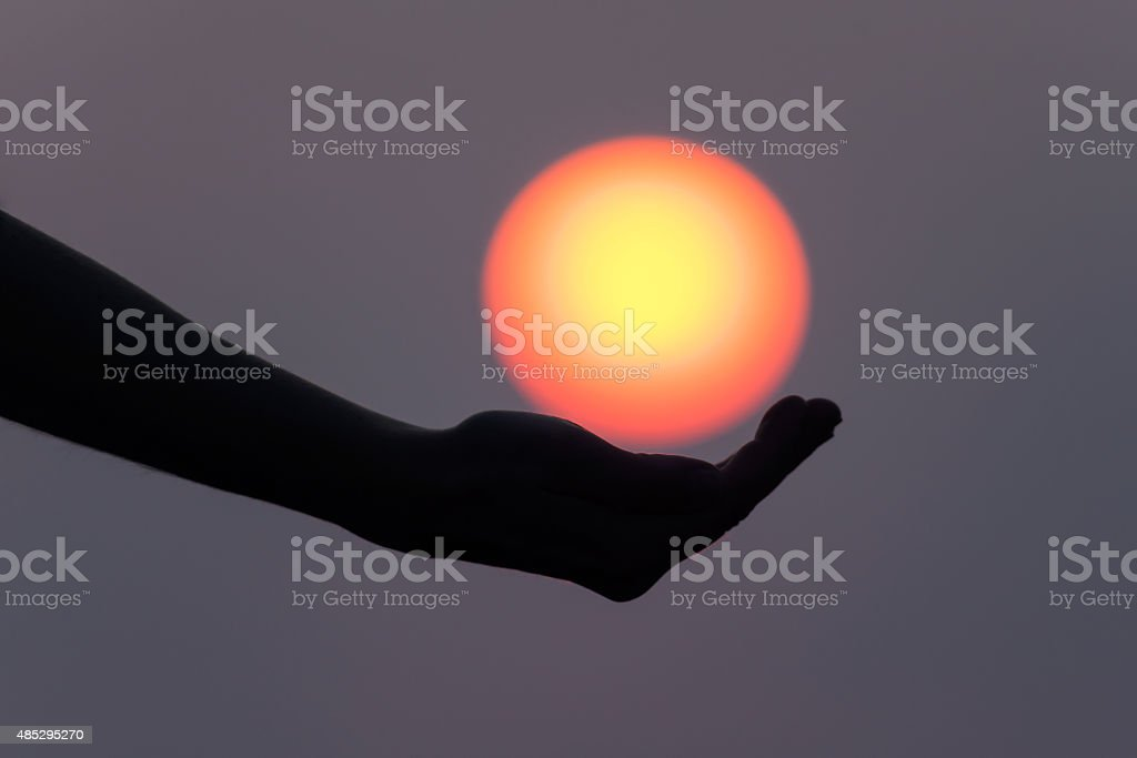 Playing with the sun in his hand stock photo