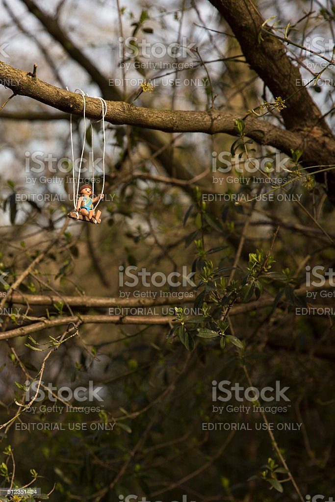 Playmobil figurine of a child having fun on a swing. stock photo