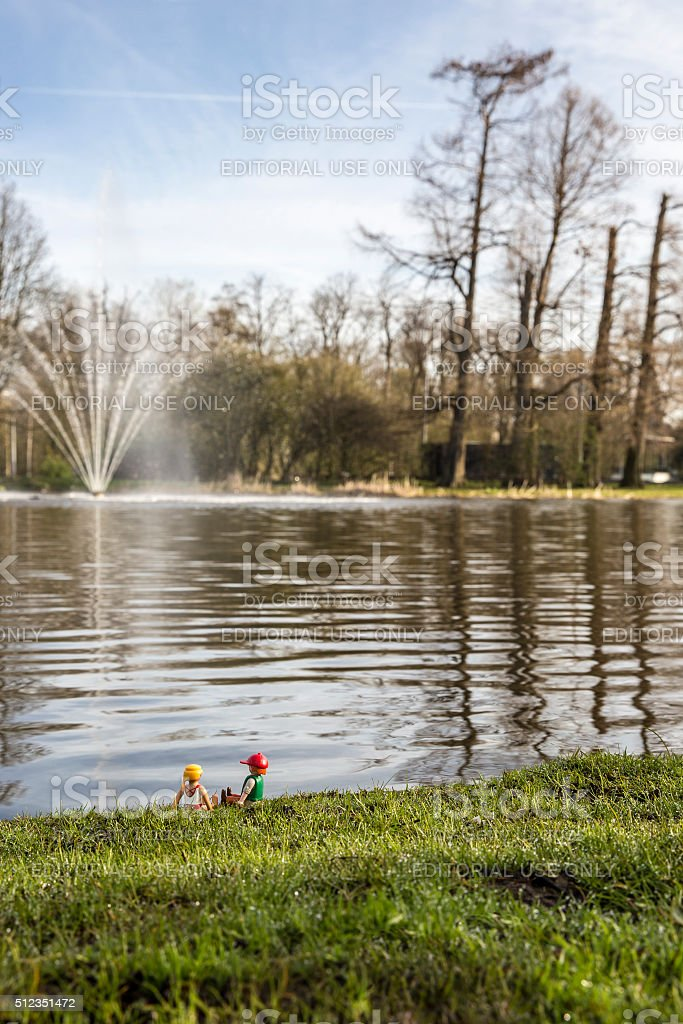 Playmobil man and woman figurines sitting by a lake stock photo