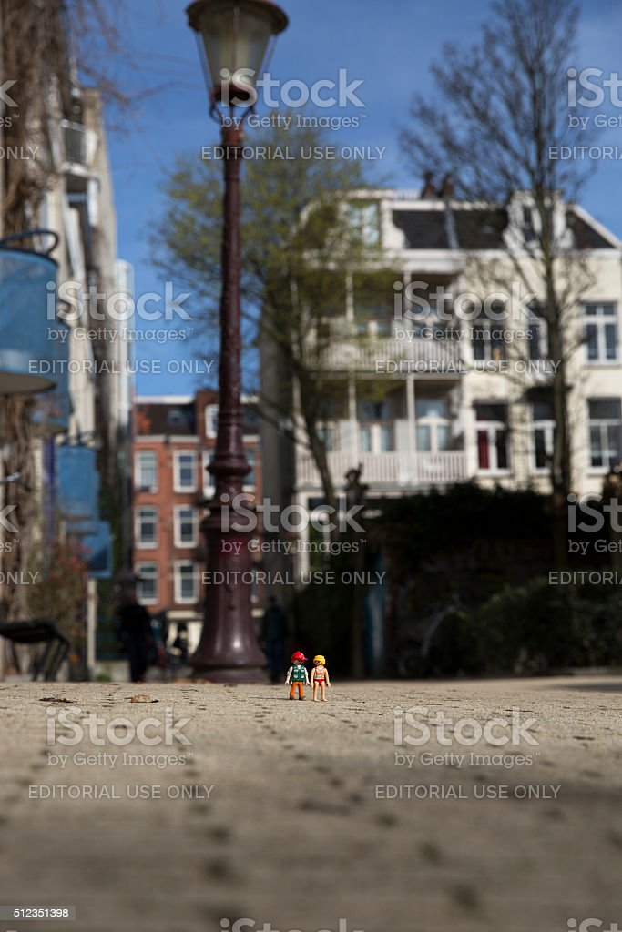 Playmobil man and woman figurines walking together in the street stock photo