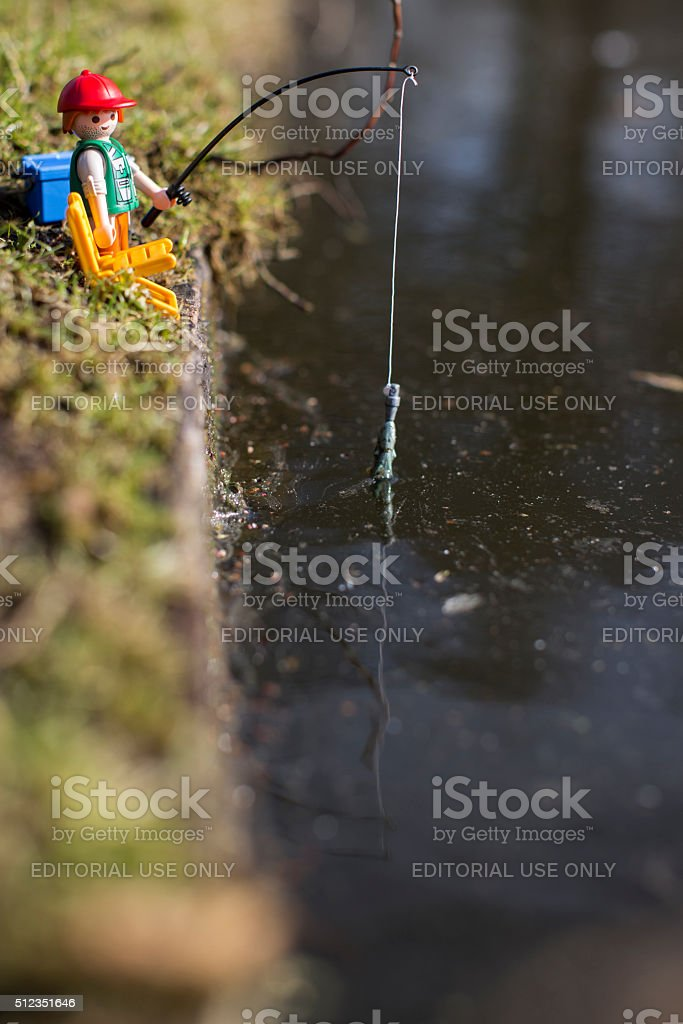 Playmobil man figurine fishing by the river. stock photo