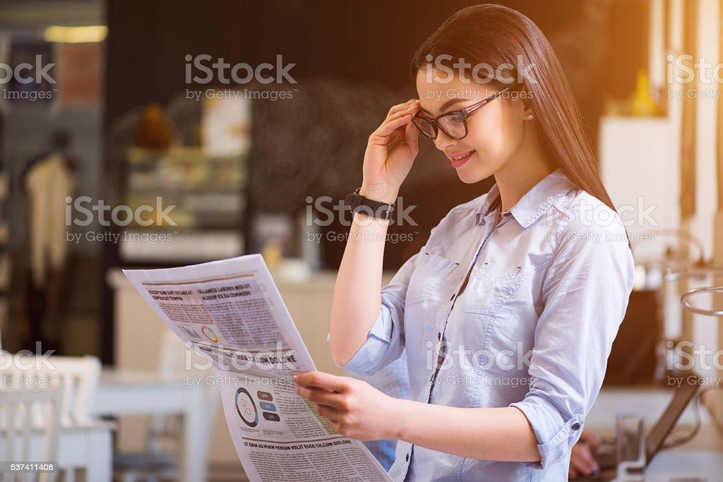Pleasant  beautiful woman reading newspaper stock photo
