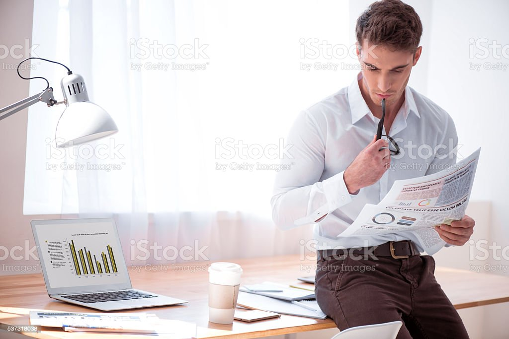 Pleasant brutal man reading newspaper stock photo