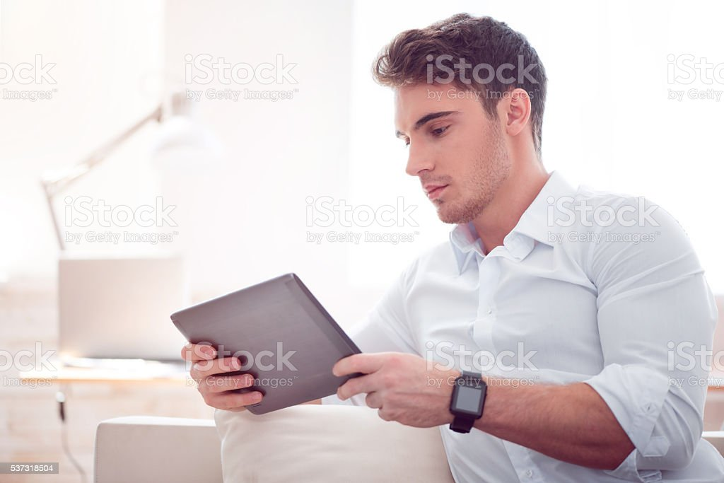 Pleasant brutal man using tablet stock photo