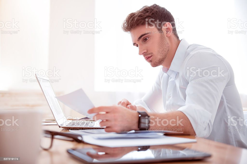 Pleasant busy man sitting at the table stock photo