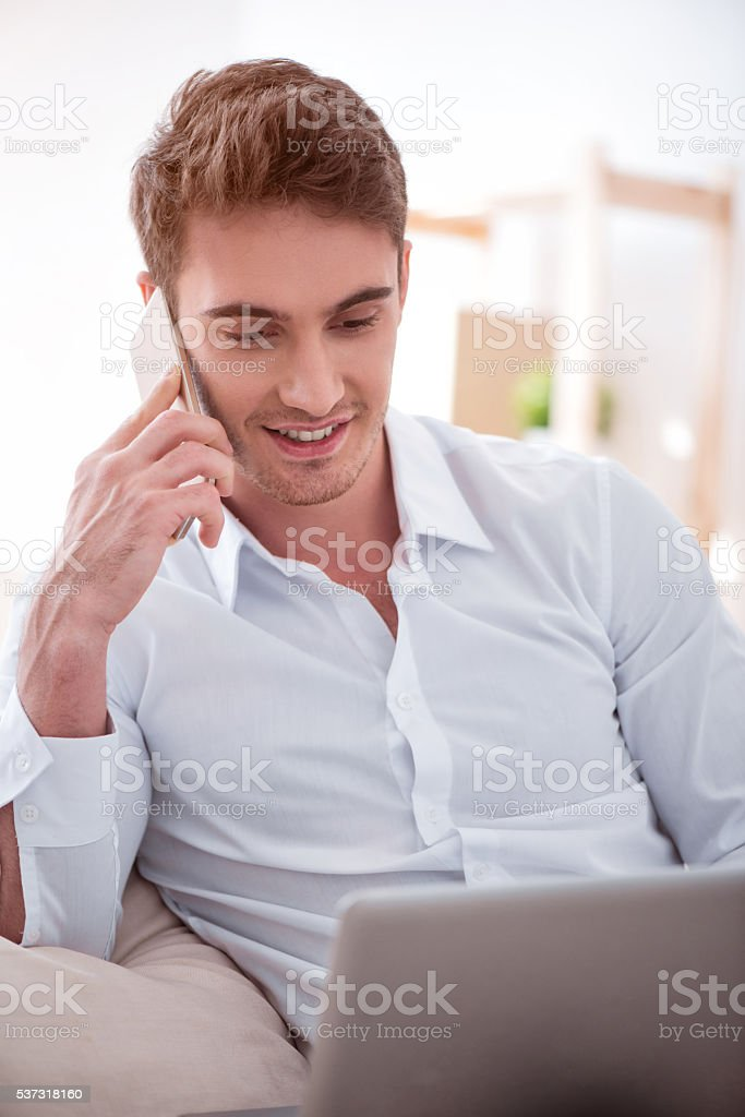 Pleasant cheerful man talking on cell phone stock photo