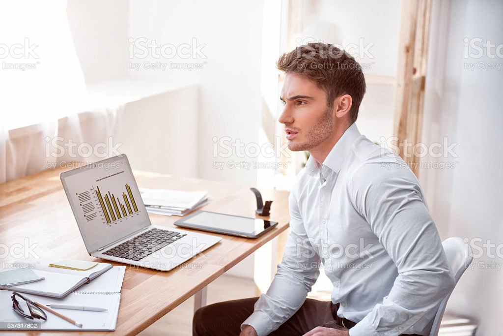 Pleasant concentrated man sitting at the table stock photo