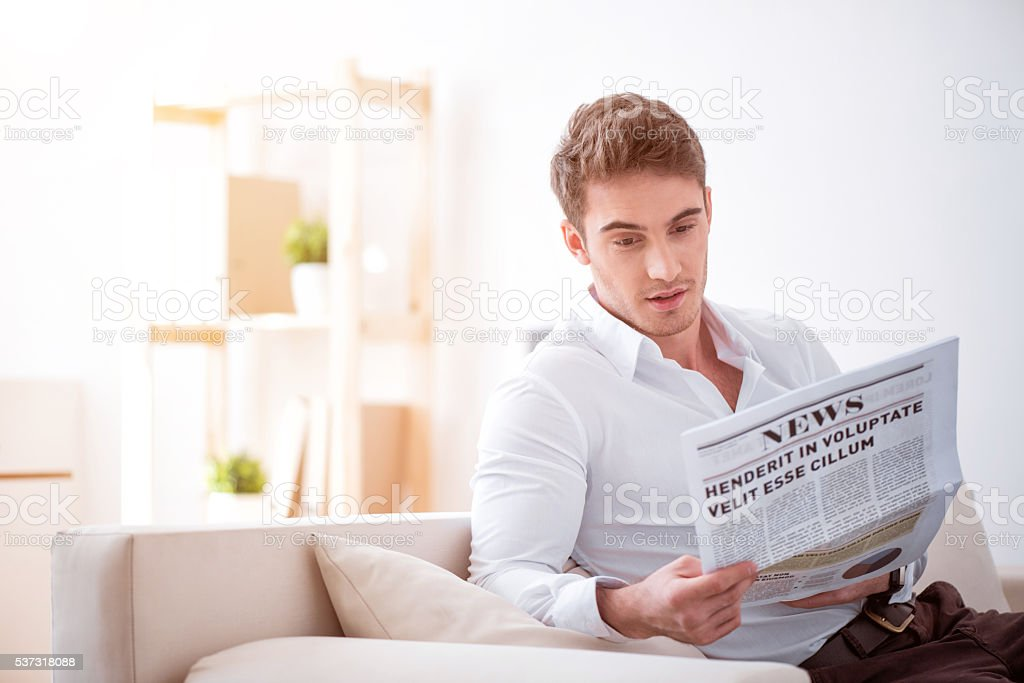 Pleasant delighted man reading newspaper stock photo