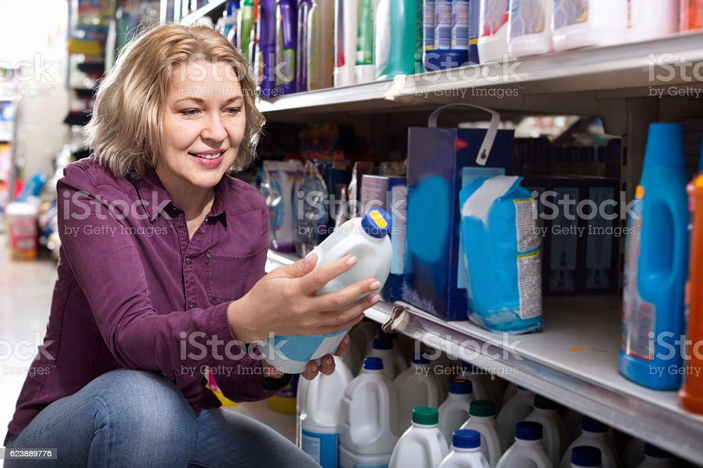 Pleasant  female with selecting fabric conditioner stock photo