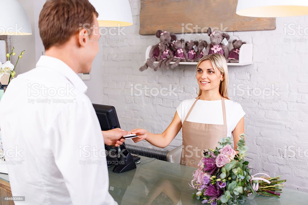 Pleasant florist serving client stock photo