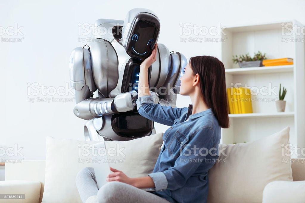 Pleasant girl touching robot stock photo