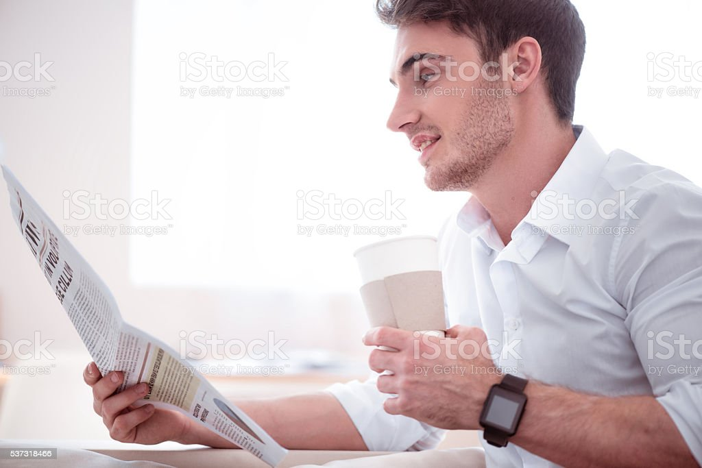 Pleasant handsome man drinking coffee stock photo