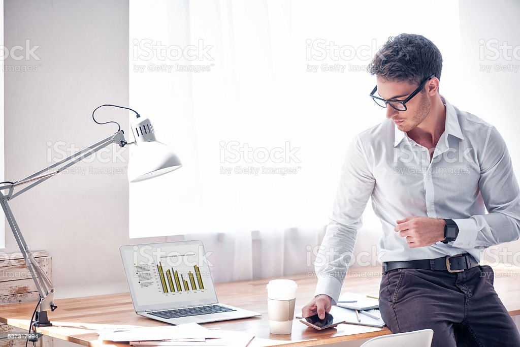 Pleasant handsome man leaning on the table stock photo