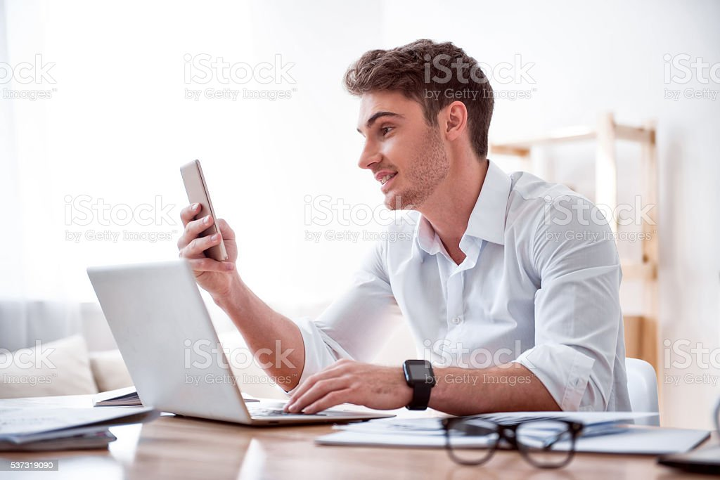 Pleasant handsome man sitting at the table stock photo