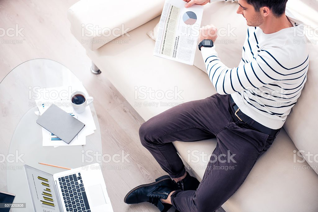 Pleasant  handsome man sitting on the sofa stock photo