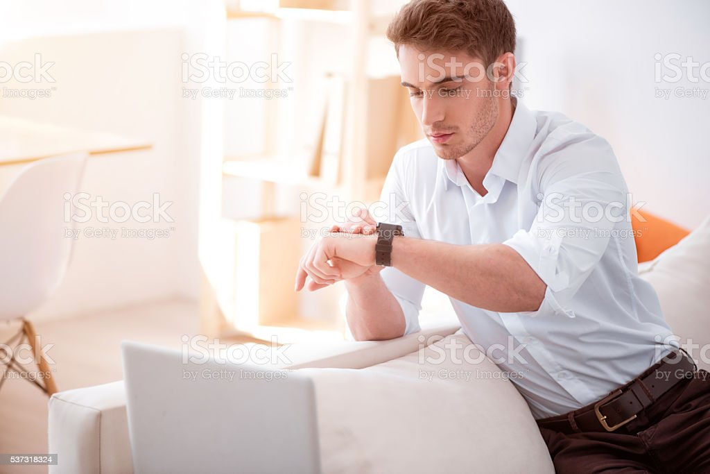 Pleasant handsome man using smart watch stock photo