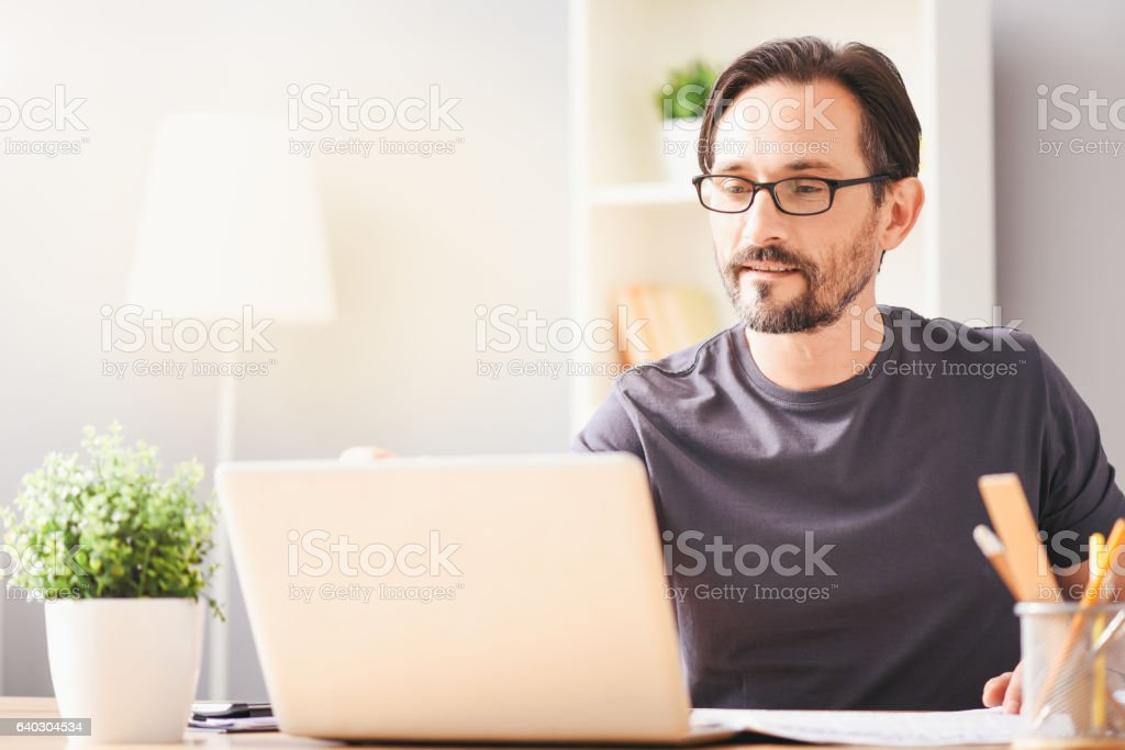 Pleasant invlved man workign on the laptop stock photo