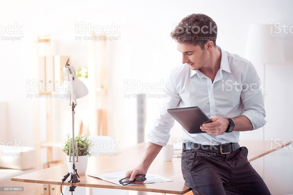 Pleasant man holding tablet stock photo