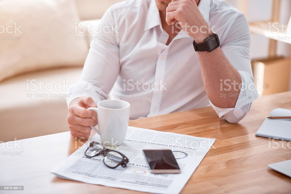 Pleasant man sitting at the table stock photo