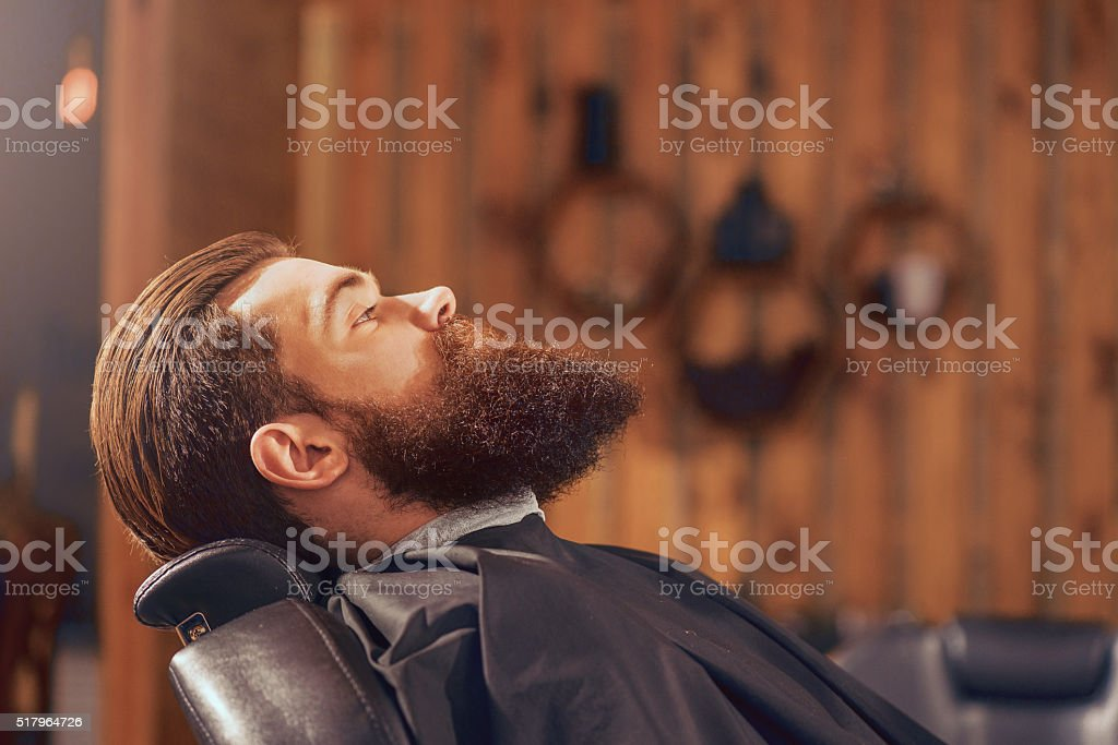 Pleasant man sitting in the barbershop stock photo