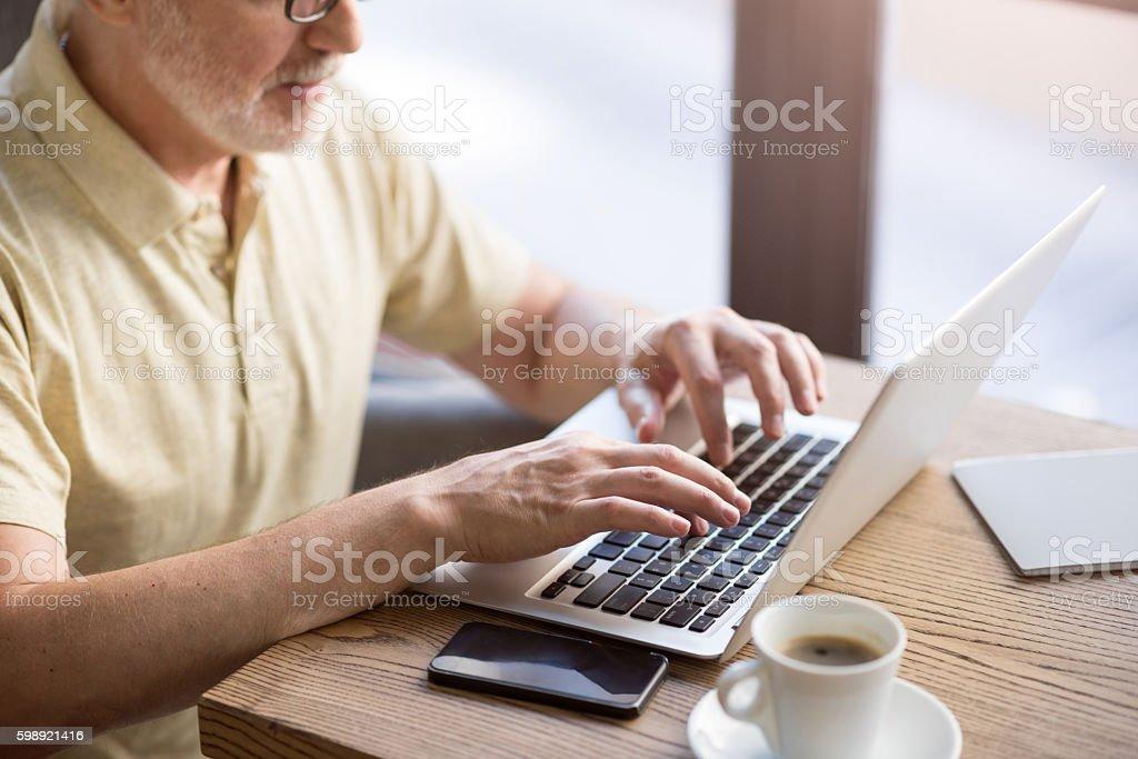 Pleasant man using laptop stock photo