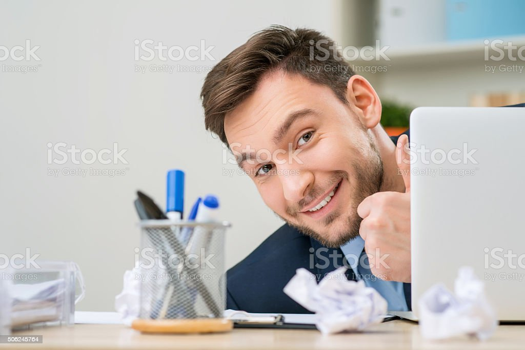 Pleasant office worker hiding behind laptop stock photo