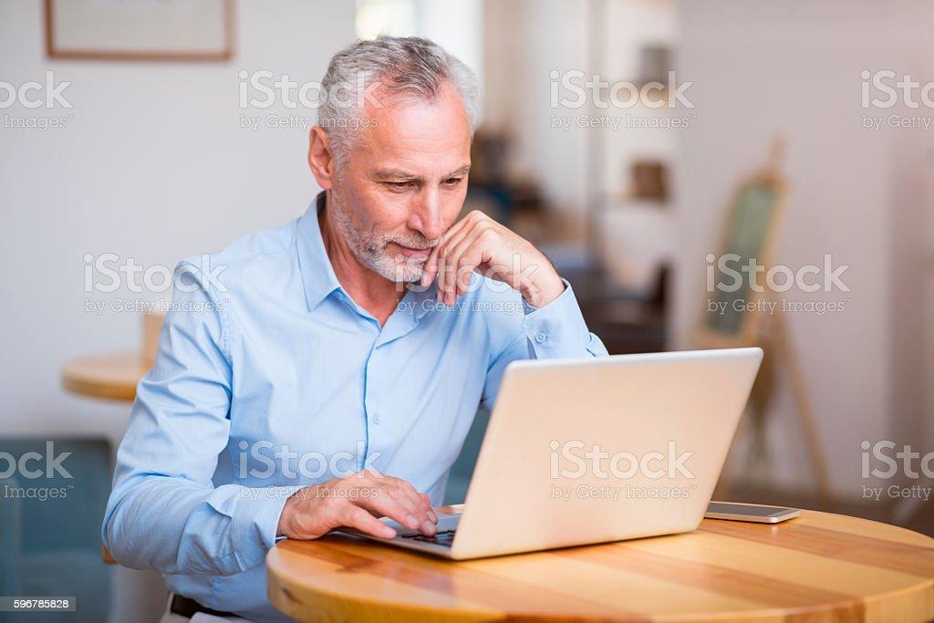 Pleasant senior man using laptop stock photo
