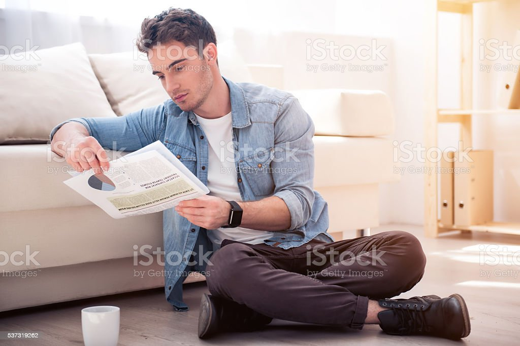 Pleasant  serious man sitting on the floor stock photo