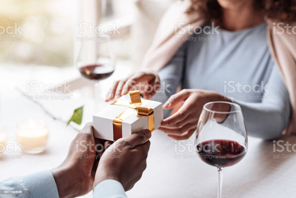 Pleasant shy African American man congratulating his girlfriend stock photo