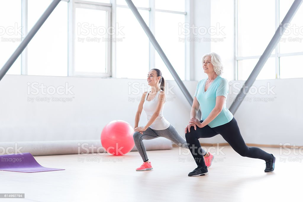 Pleasant slim women doing an exercise simultaneously stock photo