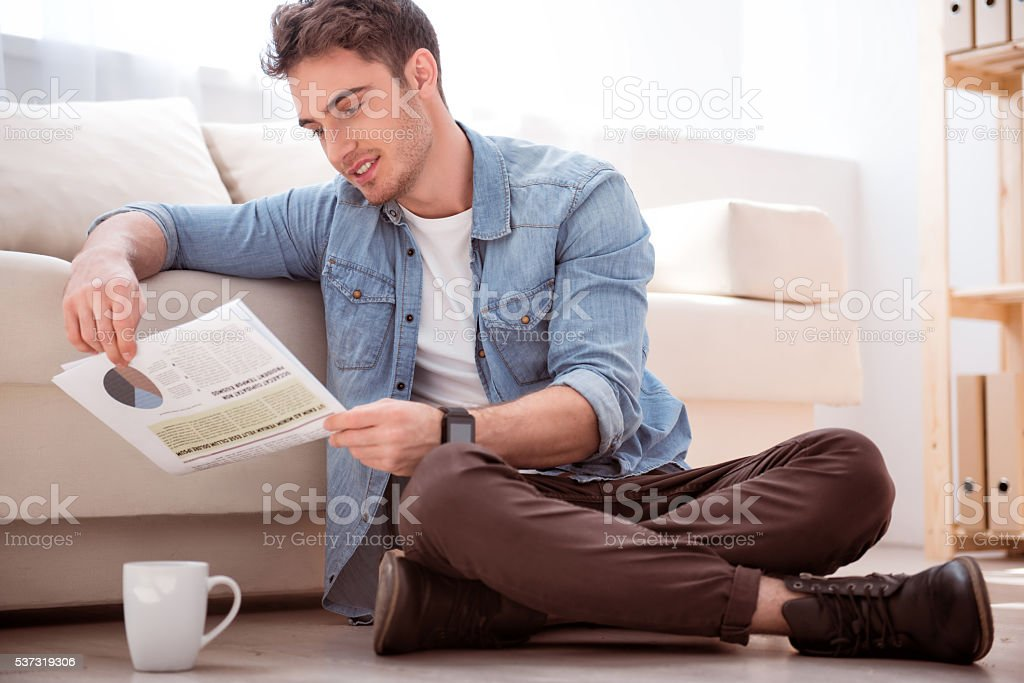 Pleasant smiling  man sitting on the floor stock photo