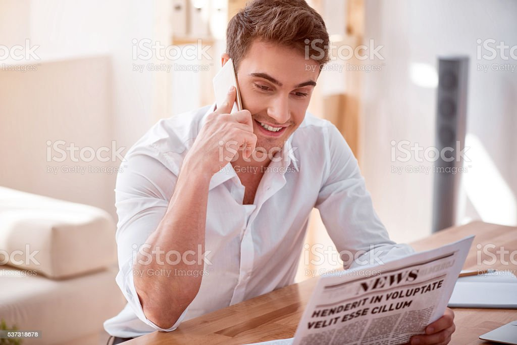 Pleasant smiling man talking on cell phone stock photo