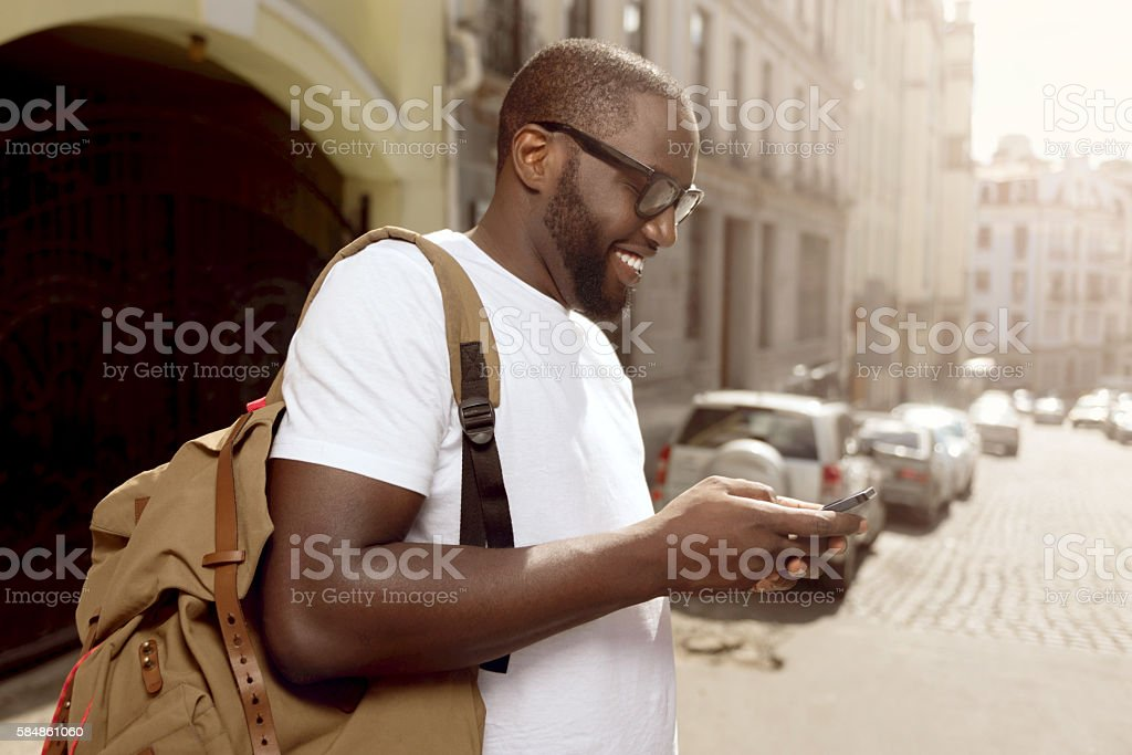 Pleasant smiling man using cellphone stock photo