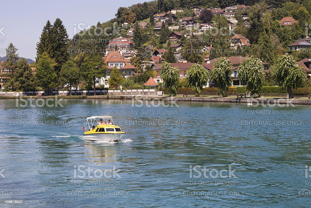 Pleasure boat slowly moves upstream on the Aare River royalty-free stock photo
