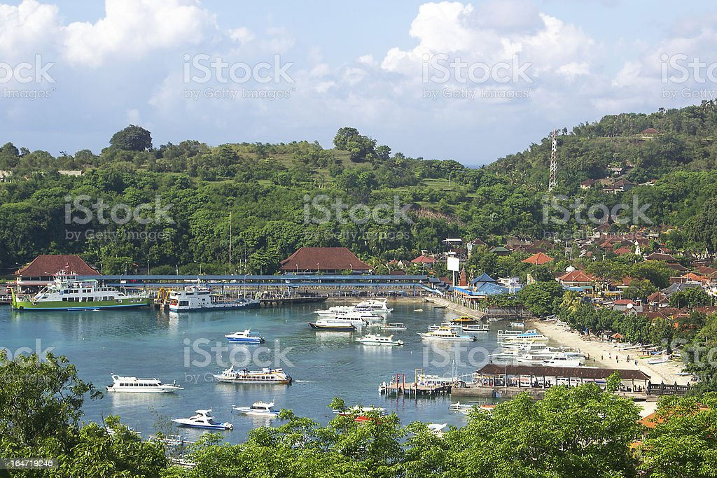 Pleasure boats in sheltered bay with resort or village royalty-free stock photo