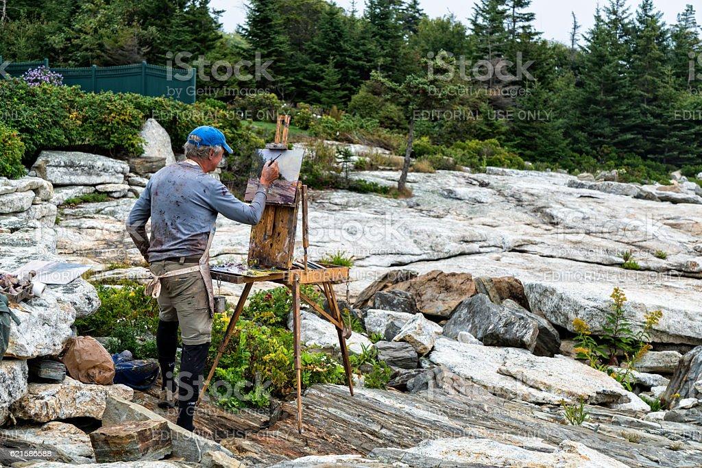 Plein air painter at ocean edge in Maine stock photo