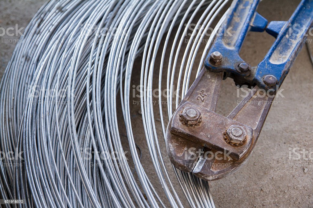 Pliers cutting rebar and thick galvanised aluminium iron metal wire. stock photo